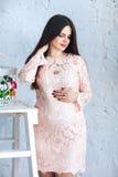 De jonge zwangere vrouw in roze kleding heeft haar handen op haar buik gezet, weg kijkend tegen een witte bakstenen muur Stock Afbeeldingen