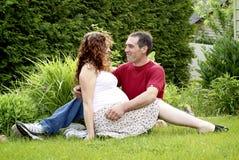 De jonge Zwangere Zitting van het Paar samen Stock Afbeeldingen