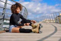 De jonge zwarte meisjeszitting op stedelijke brug en zet op vleten Vrouw met afrokapsel het rollerblading op zonnige dag stock foto's