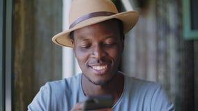 De jonge zwarte mens zit in een in koffie stock footage