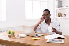 De jonge zwarte mobiele telefoon van de zakenmanvraag in modern wit bureau royalty-vrije stock fotografie