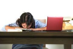 De jongelui beklemtoonde en frustreerde het Aziatische Amerikaanse tienerstudent werken met handboeken en laptop computer aan ove royalty-vrije stock fotografie