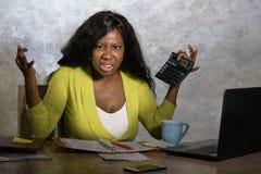 De jongelui beklemtoonde en overweldigde zwarte afro Amerikaanse vrouw die binnenlandse boekhouding met verstoord calculatorgevoe stock foto