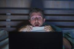 De jongelui deed schrikken en beklemtoonde mens die in bed Internet-verschrikkings op film de letten laat - nacht met laptop binn stock afbeelding