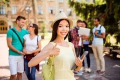 De jongelui die Aziatische student chrming houdt tablet en toont als s royalty-vrije stock foto's