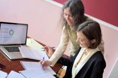 De jongelui kleedde smartly dame helpt een andere jonge dame om met documenten te werken, vormen en teken vullen Zij zitten samen royalty-vrije stock foto