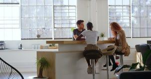 De jongelui koelt mengen-ras commercieel team die en in cafetaria van modern bureau 4k plannen zitten stock video