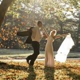 De jongelui in liefde wed koppelt onlangs het ontspannen op gebied in gouden middagzonlicht stock afbeelding