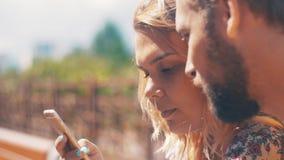 De jongelui in liefdepaar die smartphone gebruiken zit op bank De zonnige dag van de zomer talking stock videobeelden