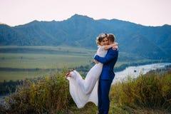 De jongelui onlangs wed koppelt, bruid en bruidegom het kussen, koesterend op perfecte mening van bergen, blauwe hemel royalty-vrije stock fotografie