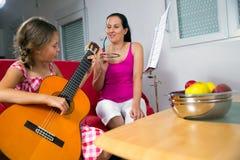 De jongelui preteen thuis meisje die gitaarles hebben Royalty-vrije Stock Afbeeldingen