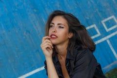 De jongelui suntanned vrouw in een korte bovenkant en overhemd met het mooie moderne samenstelling en haar stellen tegen blauwe h Royalty-vrije Stock Fotografie