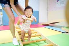 De jongelui weinig glimlachende Aziatische baby geniet van speel in jong geitjespeelplaats stock foto