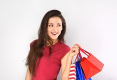 De jongelui wekte toothy glimlachende vrouw die met het winkelen zakken op op lege exemplaar ruimte blauwe achtergrond kijken stock foto's