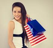 De jongelui wekte toothy glimlachende vrouw in manier witte kleding met op het winkelen zakken stock afbeelding