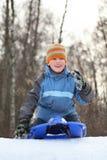De jongen is aandrijving van heuvel in de winter op sleeën van plan stock afbeeldingen