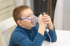 De jongen ademt met inhaleertoestel stock afbeeldingen