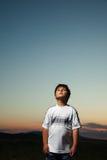 De jongen ademt verse lucht in de bergen bij zonsondergang Royalty-vrije Stock Afbeeldingen