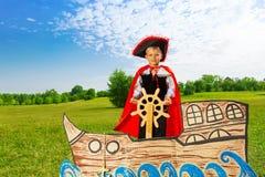 De jongen als piraat bevindt zich op schip en houdt het roer royalty-vrije stock foto's