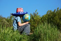 De jongen in Amerikaanse vlaghoed zit en houdt bol stock fotografie