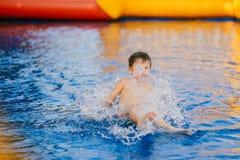 De jongen baadt in de kinderen` s pool jongen het spelen in de opblaasbare pool Royalty-vrije Stock Afbeelding