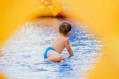 De jongen baadt in de kinderen` s pool jongen het spelen in de opblaasbare pool door gat, kader Royalty-vrije Stock Foto