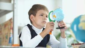 De jongen bekijkt de bol gebruikend een vergrootglas stock footage