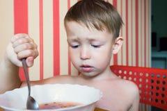 De jongen bekijkt de kom soep Stock Afbeelding
