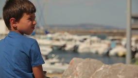 De jongen bekijkt een jacht stock footage