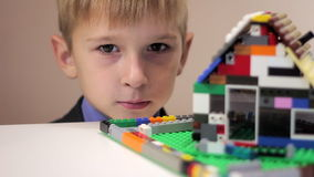 De jongen bekijkt een stuk speelgoed huis stock footage