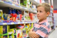 De jongen bekijkt planken met speelgoed stock afbeelding