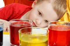 De jongen bekijkt proces van kleuring van ei royalty-vrije stock fotografie