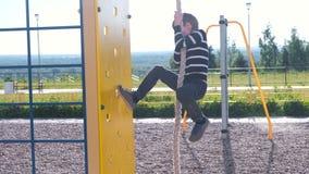 De jongen beklimt de kabel op de Speelplaats stock video