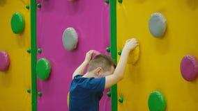 De jongen beklimt de muur stock video