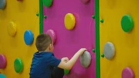 De jongen beklimt de muur stock videobeelden