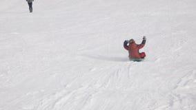 De jongen beklimt neer op een slee op een heuvel stock videobeelden