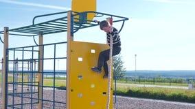De jongen beklimt op een het beklimmen muur houdend de kabel op de Speelplaats stock videobeelden