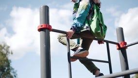 De jongen beklom omhoog op een ladderspel op de Speelplaats Hij is boven gemiddeld plan stock videobeelden