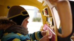 De jongen berijdt een stuk speelgoed auto op de carrousel stock videobeelden