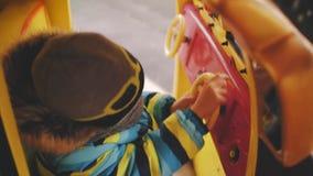 De jongen berijdt een stuk speelgoed auto op een vrolijk-gaan-ronde in een helm GLB