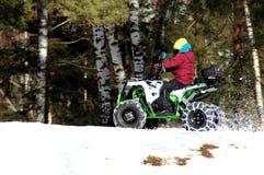 De jongen berijdt een vierling op een sneeuwhelling stock afbeelding