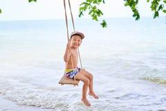 De jongen berijdt op een schommeling, op de achtergrond van de oceaan stock afbeelding