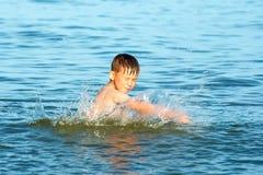 De jongen bestrooit in het zeewater op de oceaan op een de zomer dag en het golven van zijn wapens in de richting van geluk en vr royalty-vrije stock afbeelding