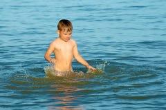 De jongen bestrooit in het zeewater op de oceaan op een de zomer dag en het golven van zijn wapens in de richting van geluk en vr royalty-vrije stock foto