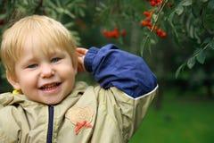 De jongen bevindt zich dichtbij de lijsterbes-boom Royalty-vrije Stock Fotografie