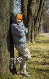 De jongen bevindt zich door de boom royalty-vrije stock foto's
