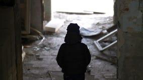 De jongen bevindt zich in een oud geruïneerd huis, de vernielings oude bouwvallige bouw stock afbeeldingen