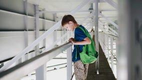 De jongen bevindt zich onder de brug op de verschansing en kijkt neer Koel licht en atmosfeer stock footage