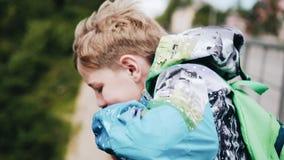 De jongen bevindt zich op de brug en kijkt neer Sterke wind emoties De jongen draagt een jasje stock videobeelden