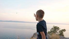 De jongen bevindt zich op een klippenberg en werpt stenen bij het overzees van de hoogte Zonsondergang stock footage